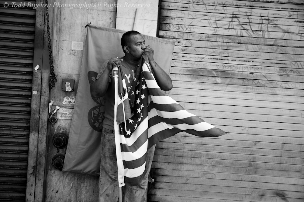 A man watching the immigrant reform rally proceed down Broadway kisses an American Flag.